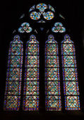 Paris, France - August 11, 2014: Big colorful stained glass window in dark interior of the Notre Dame de Paris cathedral — Stock Photo