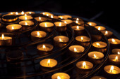 Candles burn in dark interior of Catholic cathedral — Foto Stock