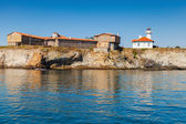 Lighthouse and old wooden buildings on Island — Stok fotoğraf