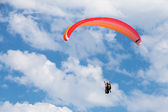 Red paraglider in the blue sky with clouds — Photo