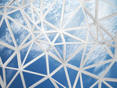 3d wired construction with chaotic triangles shape on blue sky — Foto Stock