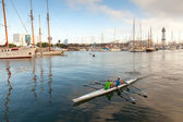 Twin sport racing rowing boat goes in Barcelona port harbor — Stock Photo