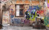 Old courtyard walls painted with colorful chaotic graffiti — Stock Photo