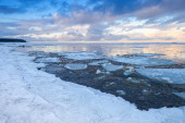 Winter coastal landscape with ice fragments on still water — Stock Photo