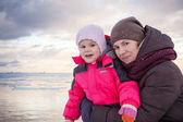 Caucasian family outdoor portrait on winter sea coast, young mother hugs her baby girl in pink jacket — Stock Photo