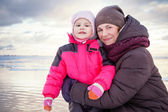 Caucasian family outdoor portrait on the winter sea coast, young mother hugs her little baby girl in pink jacket — Stock Photo