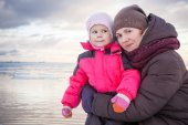 Caucasian family outdoor portrait on winter sea coast, young mother hugs her little baby girl in pink jacket — Stock Photo