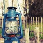 Old blue kerosene lamp hangs on wooden outdoor fence — Stock Photo #61666689