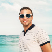 Young smiling man in white sunglasses on sea coast — Stock Photo