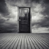 Abstract interior concept with black door and dramatic sky — Foto Stock