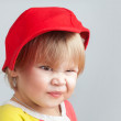 Portrait of funny smiling baby girl in red baseball cap — Stock Photo #63158723