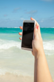 Woman using smart phone for taking photo on a beach — Stock Photo
