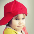 Studio portrait of funny baby girl in red baseball cap — Stock Photo #63769735