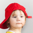 Studio portrait of funny baby girl in red baseball cap — Stock Photo #63769739