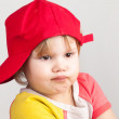Studio portrait of funny confused girl in red baseball cap — Stock Photo #63769741