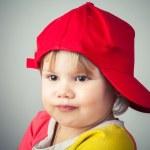Studio portrait of funny girl in red baseball cap — Stock Photo #63769743