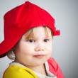 Portrait of funny little child in a red baseball cap — Stock Photo #64848573