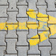Yellow arrow painted on gray cobblestone pavement — Stock Photo #65371267