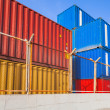 Colorful industrial cargo containers behind metal fence — Stock Photo #65991309