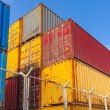 Colorful cargo containers are stacked behind metal fence — Stock Photo #65991699