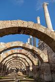 Empty corridor with arcs and columns above blue sky  — Stock Photo