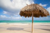 Wooden umbrella on empty sandy beach — Stock Photo