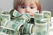 Pile of United States dollars and baby on a background — Stock Photo