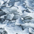 Big ice fragments covered with show on frozen river water — Stock Photo #67256937