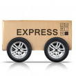 Cardboard box with signs and automotive wheels — Stock Photo #67438881