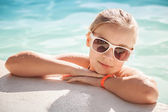 Beautiful little blond girl with sunglasses in pool — Stock Photo