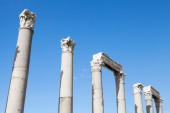Ancient columns in a row on blue sky background — Stok fotoğraf