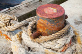 Old rusted mooring bollard with naval ropes — Stock Photo