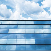 Blue mirrored glass and cloudy sky, office facade — Stock Photo