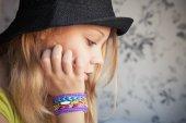 Profile portrait of beautiful blond teenage girl in black hat — Stockfoto