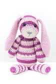 Knitted rabbit toy sitting over white background — Stock Photo