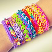 Colorful rubber rainbow loom band bracelets on wrist — Stock Photo