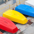 Colorful plastic boats lay on the concrete pier — Stock Photo #69388133