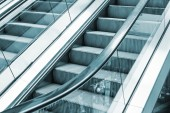 Shining metal escalator moving up, blue toned — Stock Photo