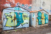 Two old rusted garages with colorful grungy graffiti — Stock Photo