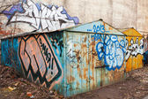 Old rusted locked garages with grungy graffiti — Stock Photo