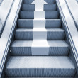 Shining metal escalator with white arrow moving up — Stock Photo #70004315