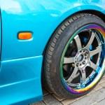 Car wheel on colorful metallic disc, closeup photo — Stock Photo #70682895