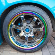 Car wheel on colorful metallic disc, close up photo — Stock Photo #70682897