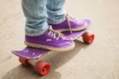 Young skateboarder in gumshoes standing on his skate — Stockfoto