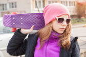 Teenage girl in sunglasses with skateboard — Stok fotoğraf