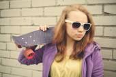 Nice blond teenage girl in sunglasses holds skateboard — Stock Photo