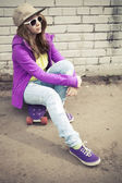 Girl in jeans and sunglasses sits on her skateboard — Stockfoto