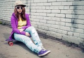 Girl in jeans and sunglasses sits on skateboard — Stock Photo