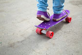 Riding skateboarder feet in jeans and gumshoes — Stock Photo