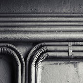 Electrical conduits mounted on old concrete wall — Stock Photo
